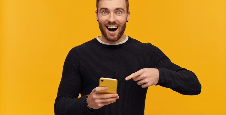bearded-happy-looking-man-with-brunette-hair-has-piercing-wearing-black-sweater-holding-pointing-finger-smartphone-copy-space-isolated-yellow-wall
