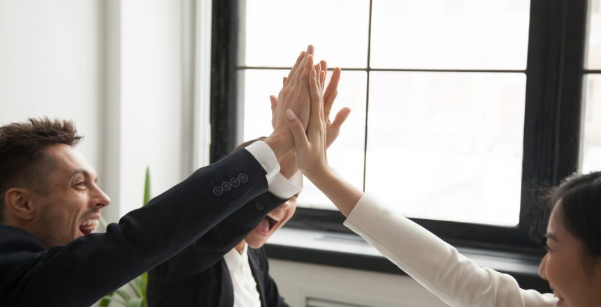 Close up of excited work colleagues giving high five screaming with happiness, reaching goal profit, making great result. Team celebrating business success raising hands up. Concept of cooperation